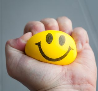 squeezing yellow smiley stress ball