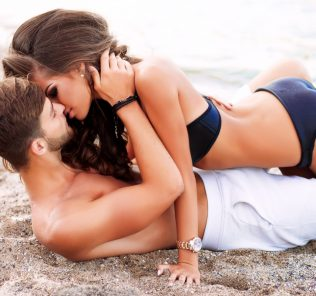 passionate couple kissing on the beach, woman on top