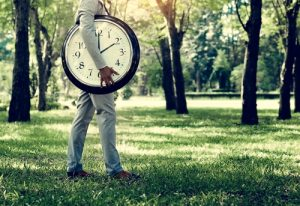 man holding large clock in forest, time