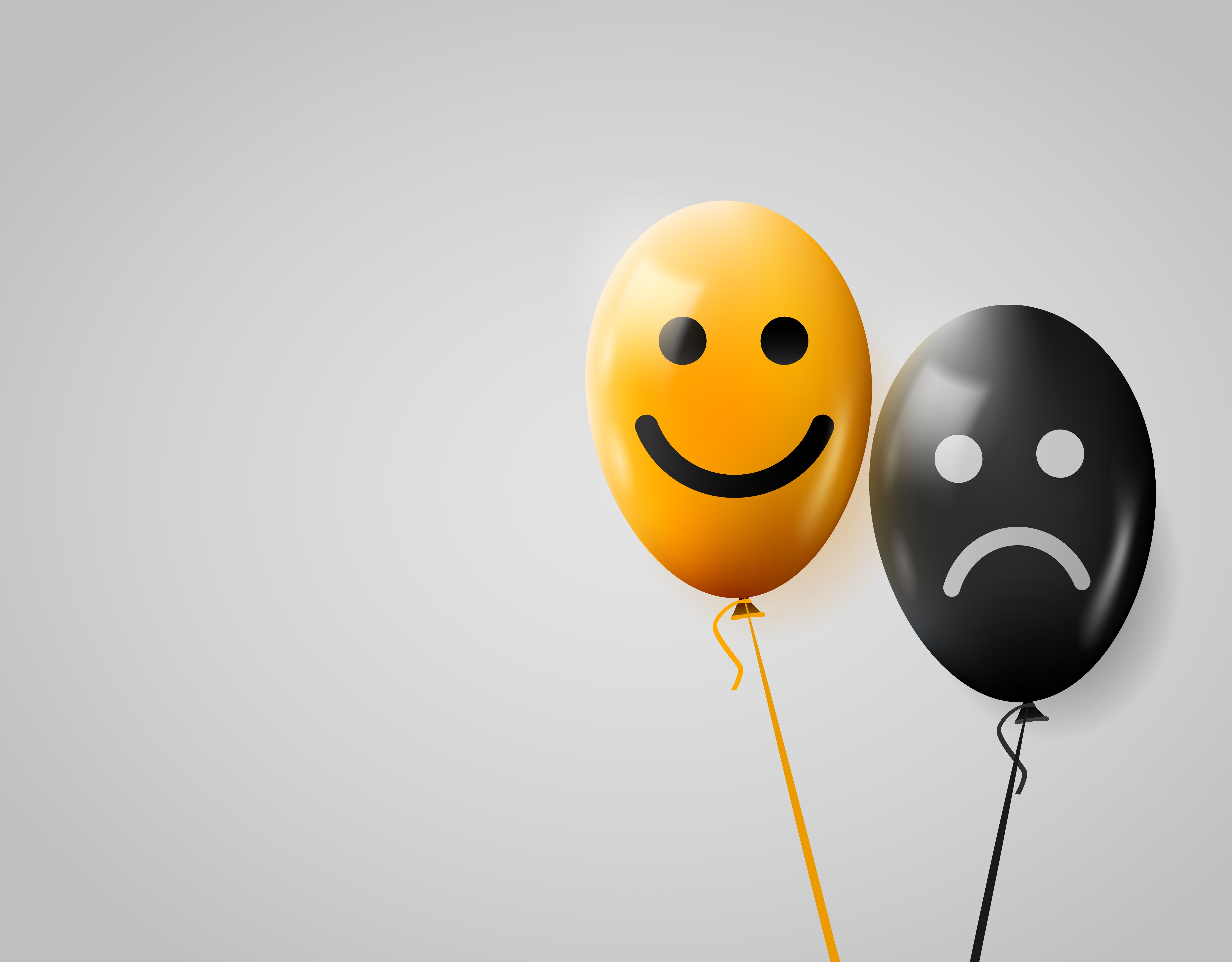 happy and sad faces on yellow and black balloons.