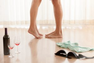 couple in hotel room getting undressed, clothes and wine on floor
