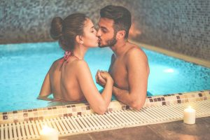 romantic couple kissing in pool with candle light
