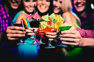 women holding out cocktails on girls night out