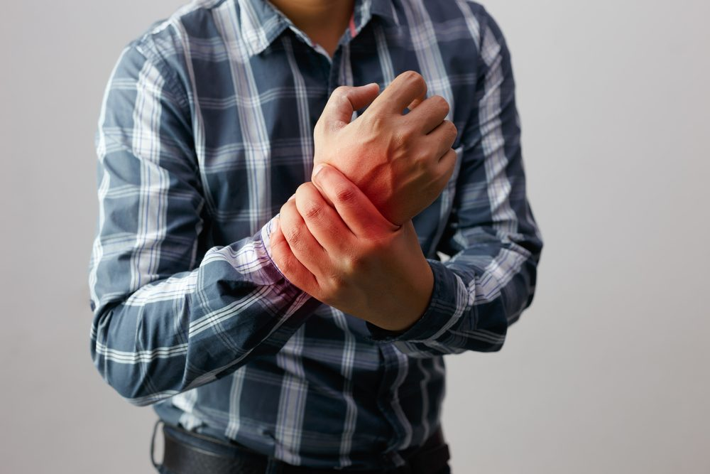 man holding his wrist experiencing joint pain