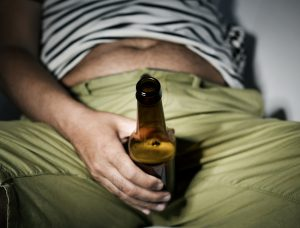 man holding a bottle of beer in front of his jean crotch