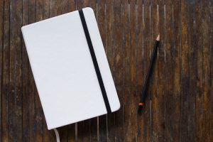 white moleskin notebook with pencil on table