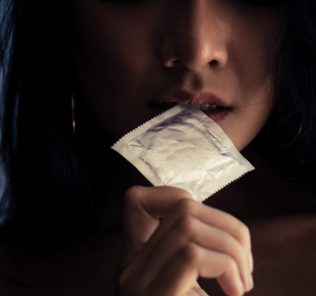 woman biting the tip of a condom packet